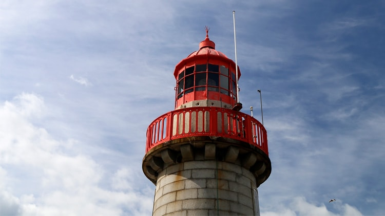 A photograph of the top of a lighthouse with a red frame and a cloudy sky in the background.
