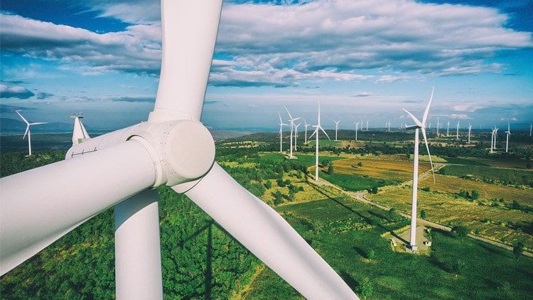 A landscape photo of wind energy turbines dotted over lush green fields.
