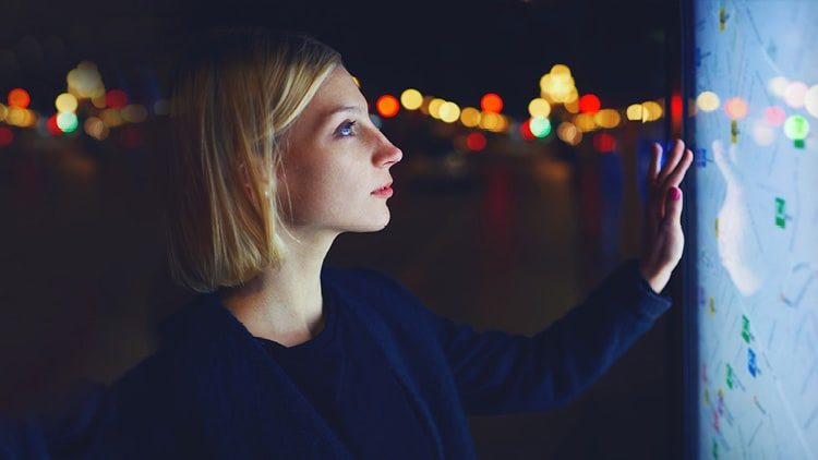 A close-up photo of a young woman using a large touchscreen in the dark.